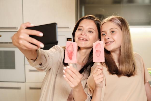 Две молодые жизнерадостные девушки с длинными волосами делают селфи на кухне, пока едят домашнее мороженое эскимо с дольками клубники