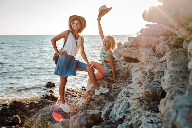 Two young cheerful women in hipsters hats on a rock on the coast of the sea. summer landscape with girl, sea, islands and orange sunlight.