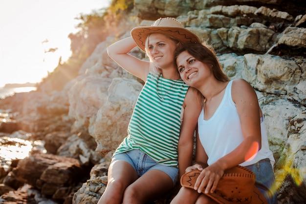海の海岸の岩の上の流行に敏感な帽子の2人の若い陽気な女性。
