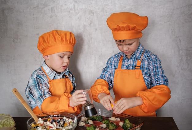 オレンジ色のスーツを着た2人の若いシェフが、ブロッコリーと野菜のサラダで赤い魚を調理します。ヨーロッパの外観の2人の兄弟。家族との夕食。