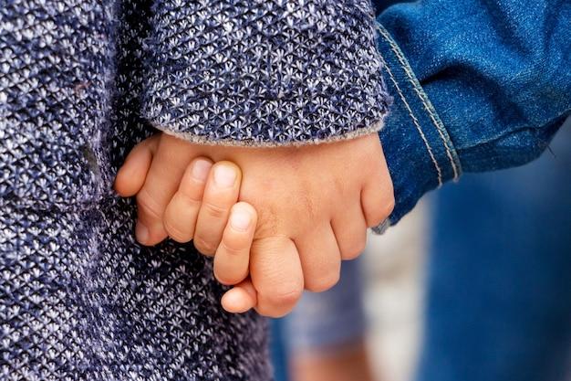2人の幼い子供が手をつないでいます。女の子は手で兄を抱きます_