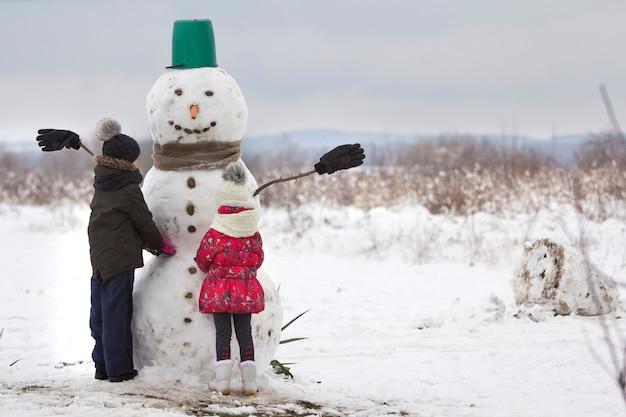 소년과 소녀 두 명의 어린 아이들이 양동이 모자, 스카프, 장갑을 끼고 텅 빈 겨울 들판 풍경과 푸른 하늘 복사 공간 배경에서 웃는 눈사람을 마무리합니다. 메리 크리스마스, 행복한 새해.