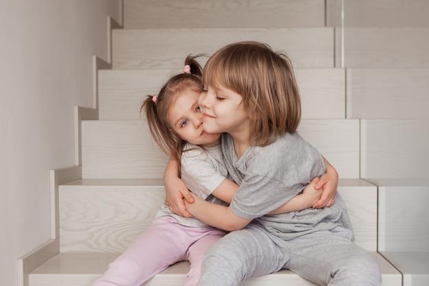 두 어린 아이 형제와 자매가 집에서 나무 계단을 껴안고 있습니다. 고품질 사진