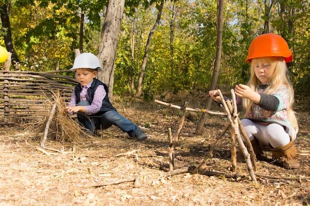 ヘルメットをかぶって、森の屋外の小枝や枝からフレームワークを作成するビルダーまたは建設労働者のふりをしている2人の幼い子供