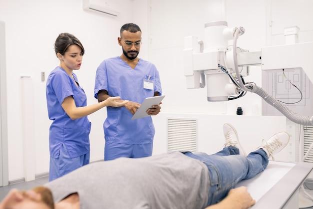 Два молодых врача в синей форме обсуждают онлайн-данные на сенсорной панели, стоя рядом с больным во время лечения