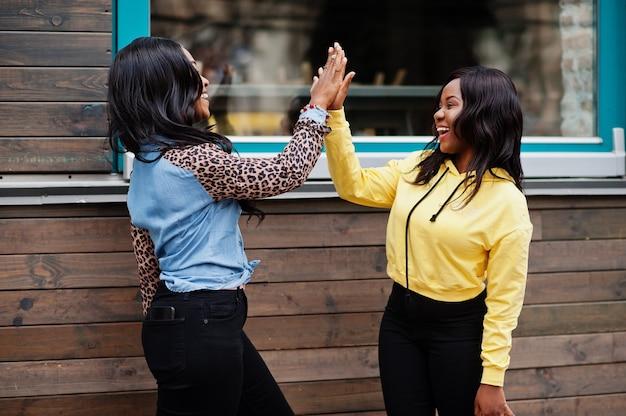 2人の若い大学のアフリカ系アメリカ人の女性の友人はお互いにハイタッチをします。