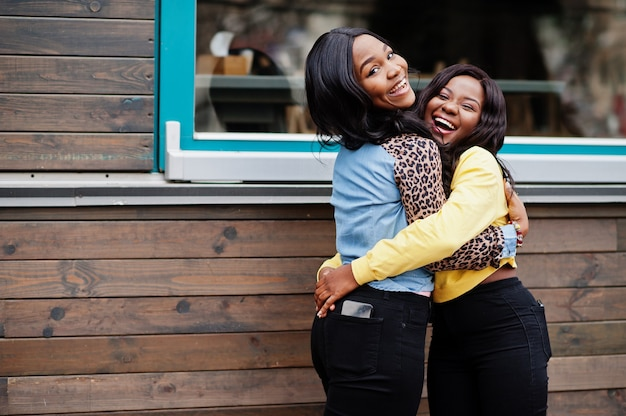 2人の若い大学のアフリカ系アメリカ人女性の友人がお互いを抱きしめます。