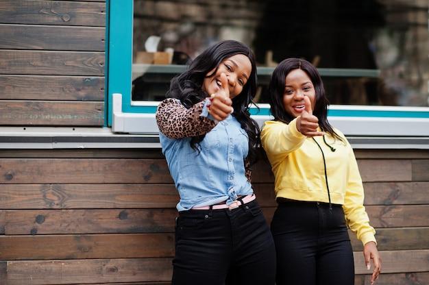 2人の若い大学のアフリカ系アメリカ人女性の友人が親指を立てます。