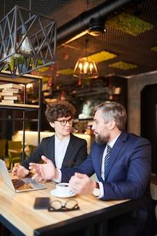 Два молодых уверенных коллеги в торжественной одежде обсуждают статистику на рабочей встрече в кафе после обеда