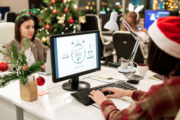 オフィスでクリスマスの日にコンピューターモニターの前で職場のそばに座っている2人の若い現代のビジネスウーマン