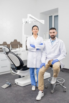 手袋と白いコートを着た2人の若い現代の歯科医が、医療機器を後ろに置いて歯科医院の職場であなたを見ています。