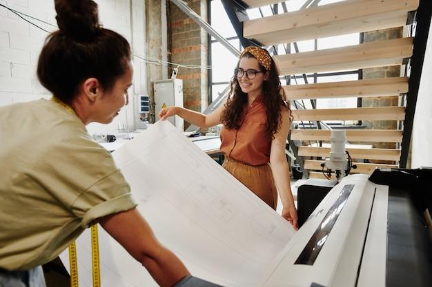 두 명의 젊은 현대 패션 디자이너가 시즌 컬렉션의 새로운 아이템을 잘라 내기 전에 큰 스케치를 인쇄합니다.