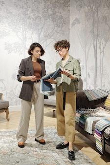 Two young contemporary female designers of interior standing in studio and consulting while choosing samples of textile for new furniture