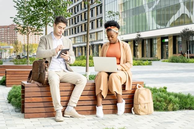 Двое молодых современных межкультурных коллег с мобильными гаджетами сидят на деревянной скамейке в парке на фоне современной архитектуры