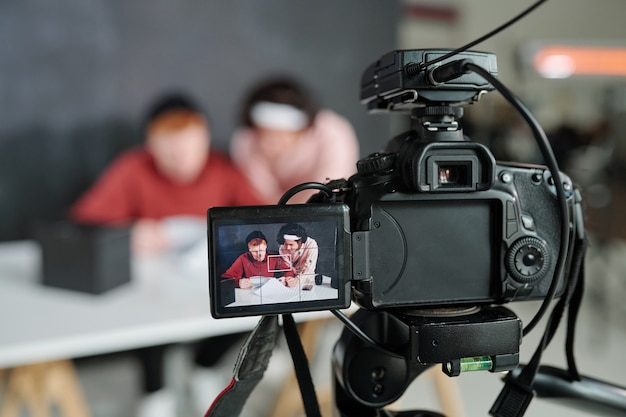 Двое молодых современных мужчин-влогеров на экране видеокамеры, стоящие перед столом в студии