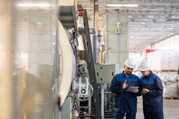 현대 공장의 두 젊은 현대 노동자가 온라인 기술 데이터 또는 작업장에서 산업 기계에 대한 세부 사항 스케치에 대해 논의합니다.