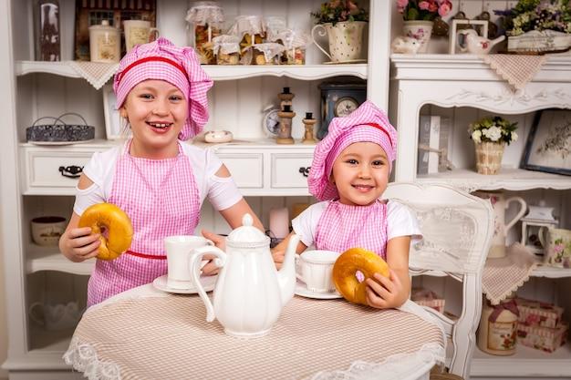 2人の若い料理人の女の子は調理されたパイに興奮しています、若い料理人はパイで