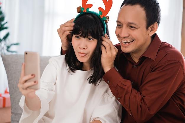 화상 통화를하고 집에서 스마트 폰을 사용하여 바보 같은 얼굴을 만드는 두 젊은 부부