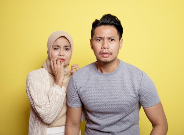 두 젊은 커플 hijab를 착용하는 여자와 표정으로 남자가 노란색 배경에 고립 된 카메라를보고 무서워