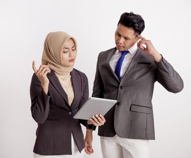 2つの若いカップルのビジネス会議は、タブレットの孤立した白い背景でプロジェクトについて話し合った