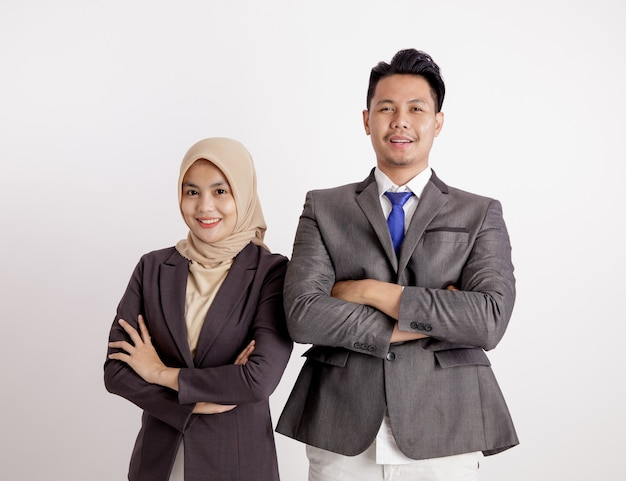 Две молодые пары бизнес, улыбаясь, скрестив руки, глядя в камеру, изолированные на белом фоне