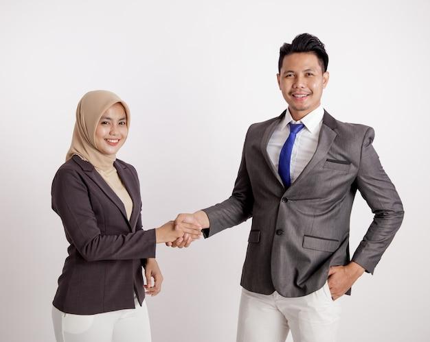 2人の若いカップルのビジネス笑顔のハンドシェイクは、カメラの孤立した白い背景を見て作業します。