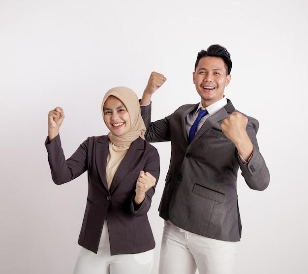 2人の若いカップルのビジネスは、カメラの孤立した白い背景を見て非常に興奮して働いています