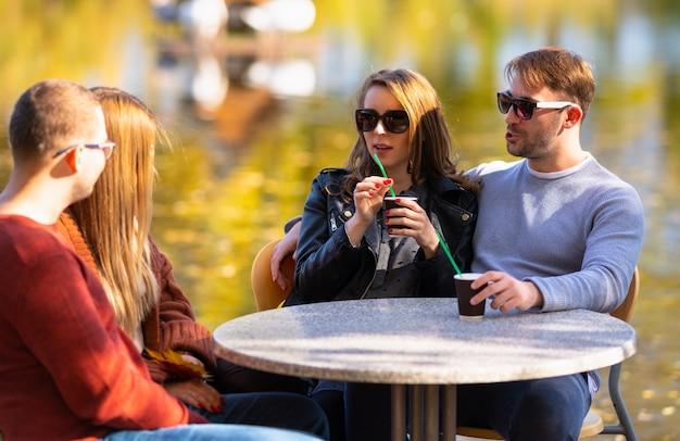 Две молодые пары пьют кофе на открытом воздухе, сидя и болтают в ресторане на открытом воздухе с видом на озеро осенью