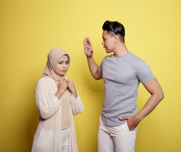 문제가있는 두 젊은 커플. 노란색 배경에 고립 된 여성이 다시는 그것을하지 않는다고 경고하는 남자