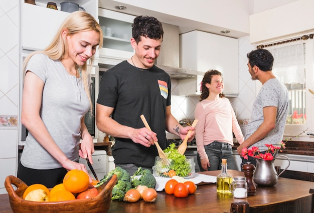 Two young couples together preparing food in the kitchen