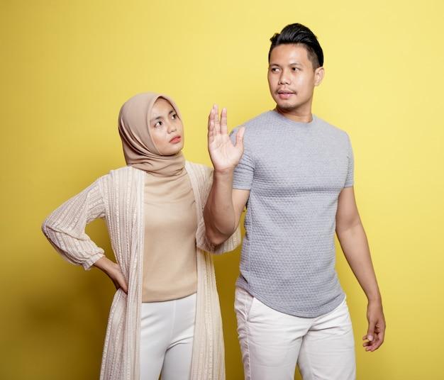 히잡을 입고 두 젊은 커플과 노란색 배경에 고립 된 여자에게 뭔가를 말하는 표정으로 남자