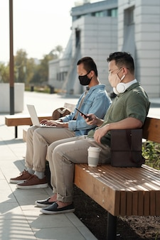 벤치에 앉아 모바일 기기를 가진 두 젊은 동료