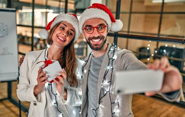 산타 모자를 쓴 두 명의 창의적인 젊은이들이 선물을 교환하고 마지막 근무일에 스마트 폰 셀카를 찍습니다.