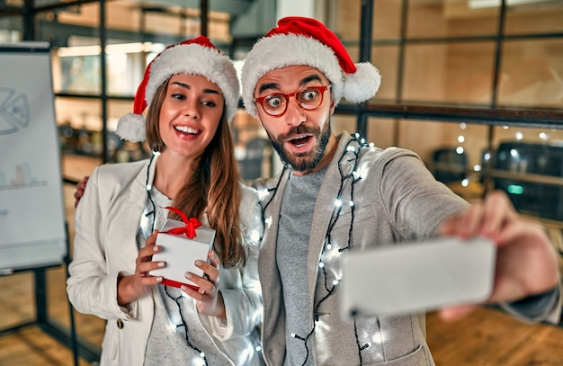 Два молодых творческих человека в шляпах санты обмениваются подарками и делают селфи на смартфоне в последний рабочий день.