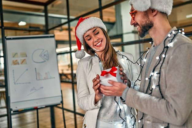 Два молодых творческих человека в шляпах санты обмениваются подарками в последний рабочий день.