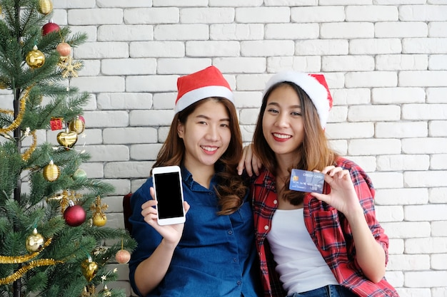 Two young cute asia women holding smart phone with blank screen and credit card for shoppi