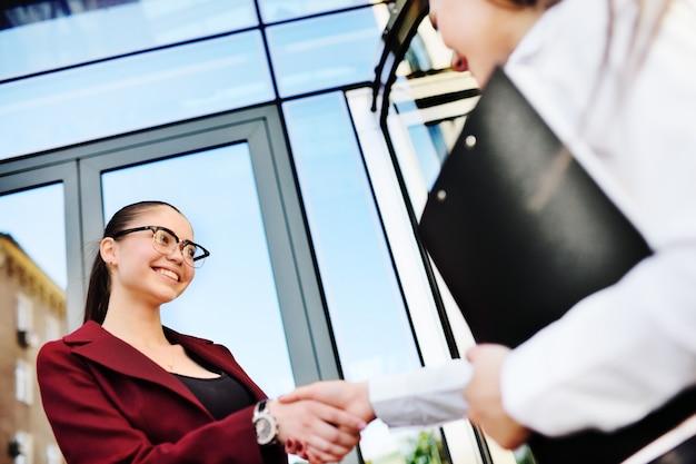 2人の若いかわいいビジネス女性が握手します。成功したトランザクション、契約、契約、ビジネス。