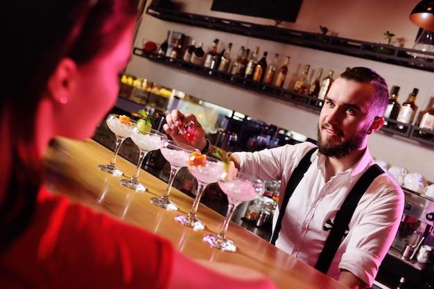 Две молодые милые девушки пьют коктейли в ночном клубе или баре, веселятся, улыбаются и разговаривают с барменом