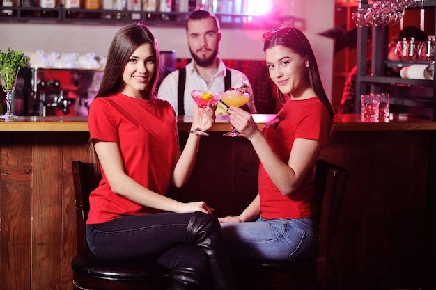 Two young cute girls drink cocktails in a nightclub or bar