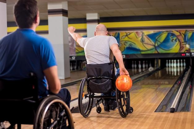 クラブでボウリングをしている車椅子の2人の若い障害者男性