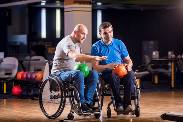 Two young disabled men in wheelchairs playing bowling in the club