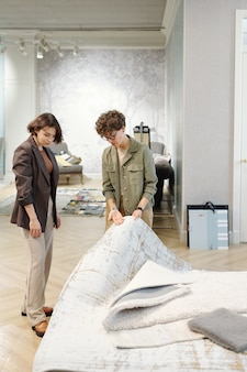 Two young elegant female designers of interior standing in studio and consulting while choosing sample of new carpet or floor coverings