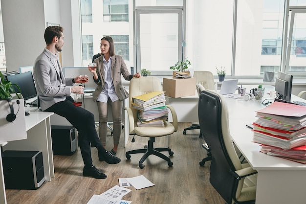 두 젊은 우아한 직장인이 휴식 시간에 직장에서 휴식을 취하고 뉴스 또는 일상적인 요점을 논의하는 동안 코냑이나 위스키를 마시 며