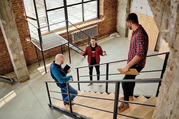 Два молодых инженера в повседневной одежде стоят на лестнице внутри недостроенного здания и слушают своего коллегу с стаканом кофе