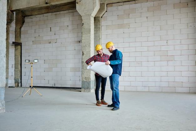 彼らが働く未完成の建物のスケッチで青写真を見ているヘルメットとカジュアルウェアの2人の若いエンジニアまたはビルダー