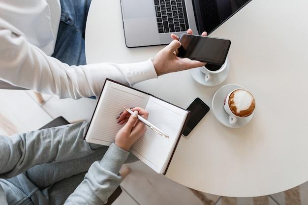 男性と女性の2人の若い起業家がオフィスのテーブルに座って金融プロジェクトについて話し合う