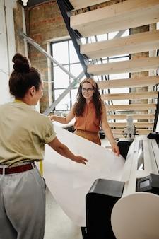 두 명의 젊은 패션 디자이너가 새 의류 품목의 스케치 또는 종이 패턴을 함께 인쇄하면서 대형 프린터에서 꺼내
