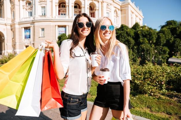 Две молодые модницы с хозяйственными сумками веселятся на открытом воздухе