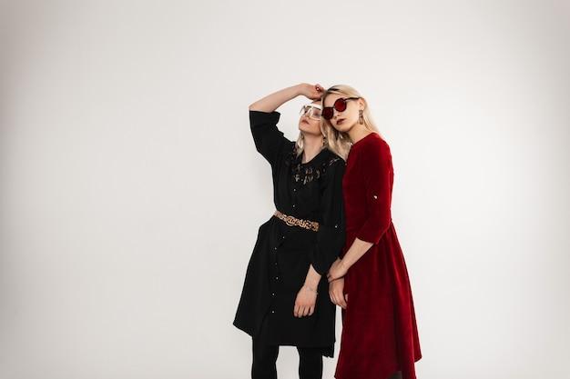 포즈를 취하는 세련된 최신 유행의 옷에 멋진 선글라스와 함께 두 젊은 유행 여자 친구 소녀 프리미엄 사진