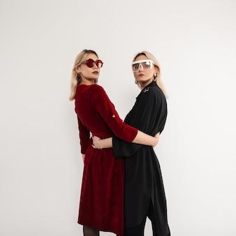 포즈를 취하는 세련된 최신 유행의 옷에 멋진 선글라스와 함께 두 젊은 유행 여자 친구 소녀